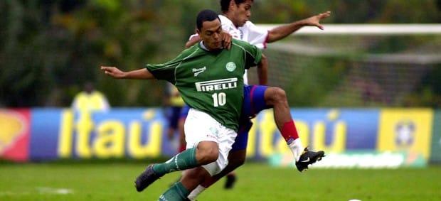 Dodô em disputa de bola vestindo a camisa do Palmeiras.